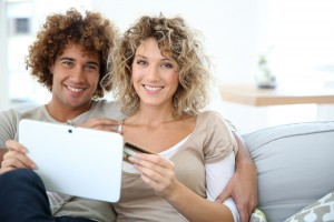 Cheerful couple at home e-shopping with tablet