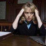 Stressed female lawyer looking at laptop